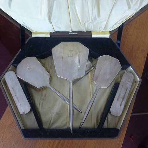 366 - A cased sterling silver 1930's dressing set comprising of 3 brushes and 2 clothes brushes, box: 6 x ...