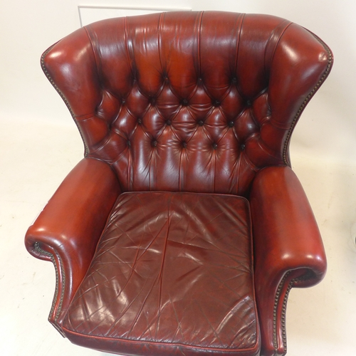 381 - A large deep red leather studded armchair on a swivel base with lion paw feet, H: 95 x W: 90 x D: 80...