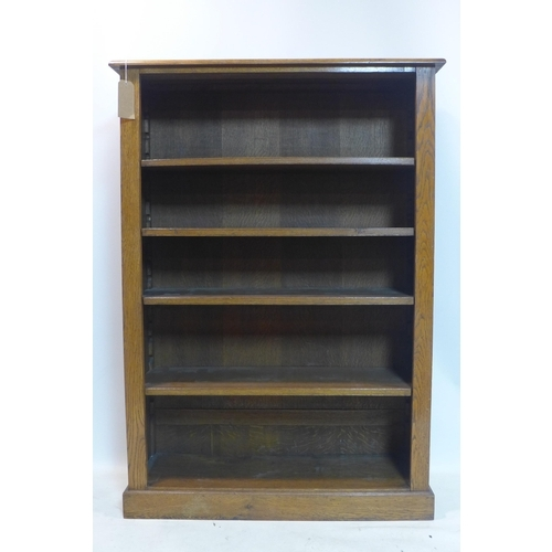 25 - An early 20th century oak open bookcase, raised on plinth base, H.153 W.109 D.35cm...