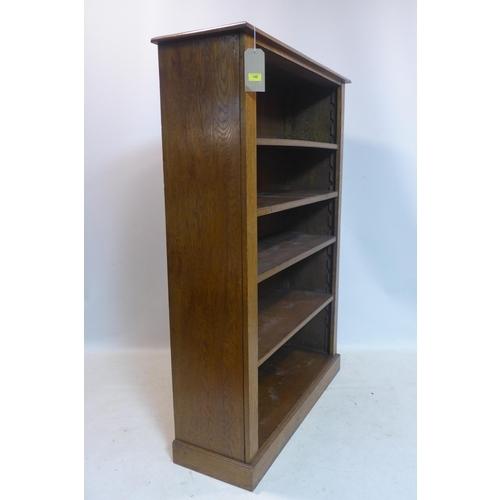 25 - An early 20th century oak open bookcase, raised on plinth base, H.153 W.109 D.35cm...