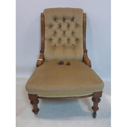 504 - A Victorian mahogany chair with velour button back upholstery, raised on turned legs and castors...