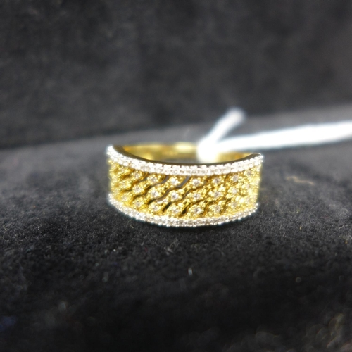 510 - An 18ct yellow and white gold ring set to the centre with a pierced lattice design studded with diam...