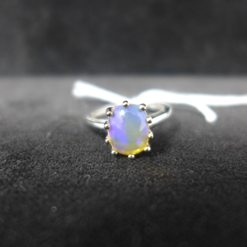 513 - A 9ct white gold ring set with an oval Ethiopian opal in a 10-claw mount (opal hues of turquoise, vi...