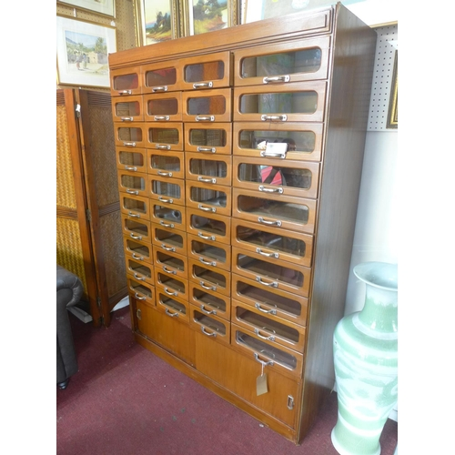 573 - A 20th century haberdashery cabinet, with forty glass fronted drawers above 2 sliding doors, H.198 W...