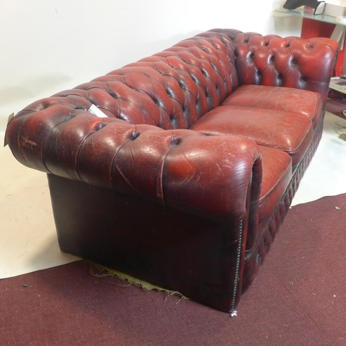 574 - A red leather chesterfield sofa...