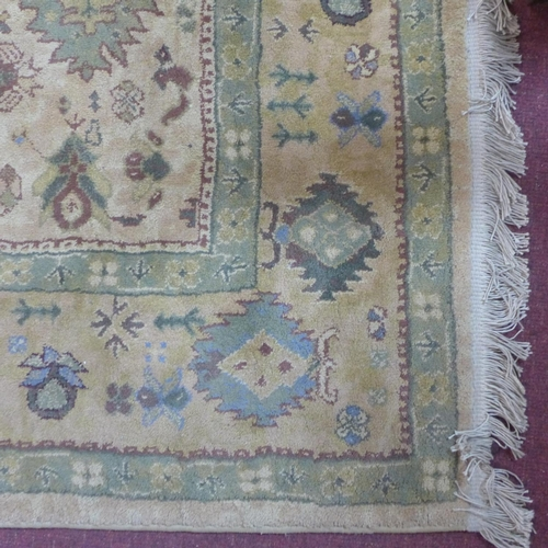 589 - A Persian style carpet with geometric design, on a beige ground, 230 x 164cm...