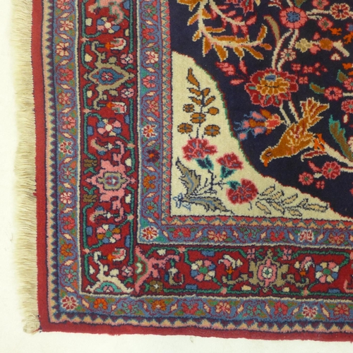 618 - A Persian carpet in pure wool decorated with a central medallion and adorned with birds and floral m...
