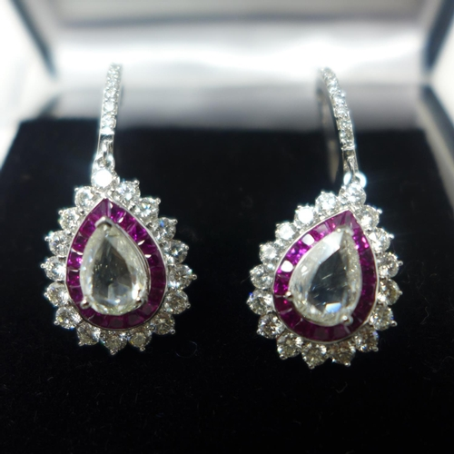 621 - A boxed pair of 18ct white gold diamond and ruby drop earrings, each earring centrally set with a pe...