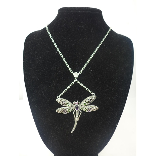 667 - A sterling silver dragonfly necklace set with an amethyst cabochon body, ruby eyes, marcasites and e...