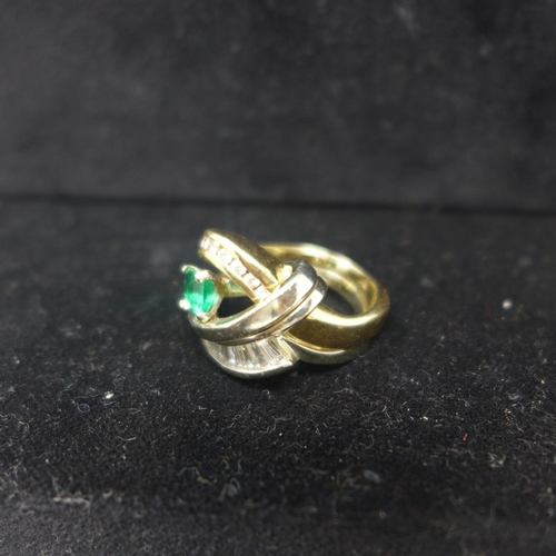 684 - A boxed 14ct yellow and white gold ring centrally set with a feceted sqaure emerald flanked by two r...