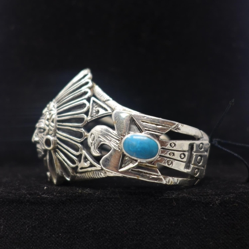 703 - A sterling silver large bangle in the form of an American Indian with turquoise cabochon panels, Dia...