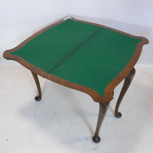 522 - An Irish walnut fold over card table, with carved shell legs...