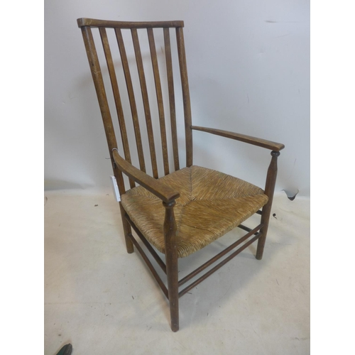 507 - A late 19th / early 20th century ladder back chair with rush seat, raised on tapering legs joined by...