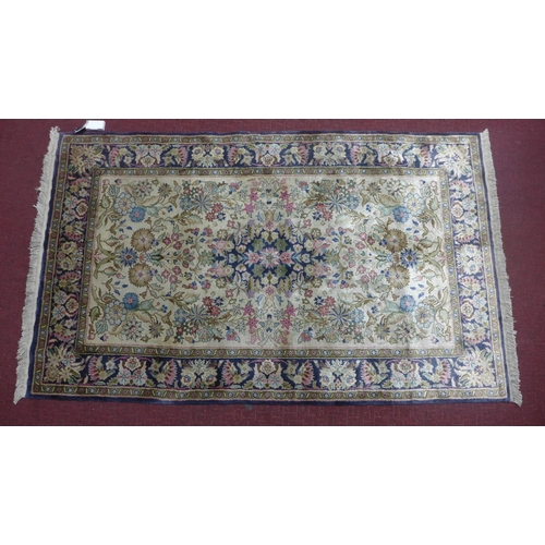 514 - A 20th century silk Tabriz rug with floral medallion, on a beige ground, contained by blue floral bo...