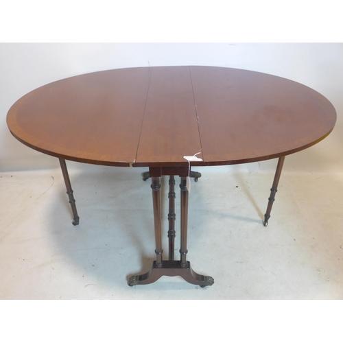 544 - A Regency style mahogany drop leaf table, raised on turned legs and castors...