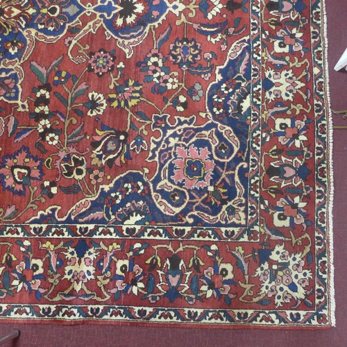 22 - A North West Persian Bakhtiari carpet, central double pendent medallion with repeating stylised span...