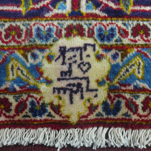 23 - A Central Persian Kashan carpet, central double pendent medallion with repeating spandrels on a roug...