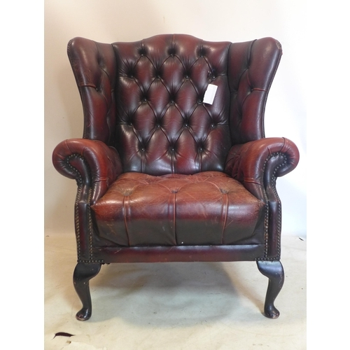 292 - A Georgian style leather wing back armchair, with label for Winchester furniture...