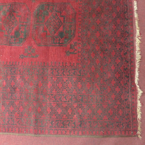 512 - A large 20th century Bokhara carpet with repeating gull motifs, on a red and black ground, contained...