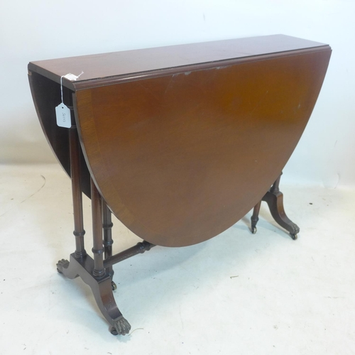 544 - A Regency style mahogany drop leaf table, raised on turned legs and castors...
