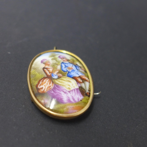 849 - A Victorian 9ct gold and hand painted porcelain brooch, decorated with a man playing the violin to a...