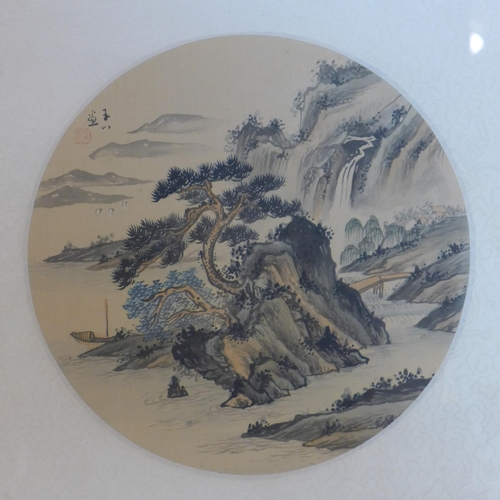 283 - A pair of Chinese glazed and framed circular ink drawings on silk depicting gnarled trees in landsca...