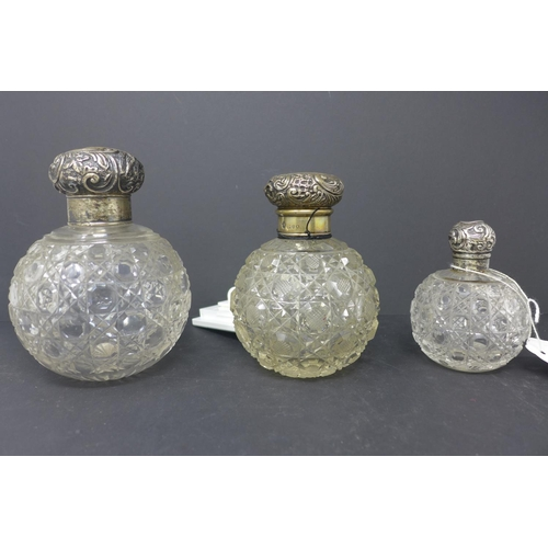 335 - Three silver topped crystal jars, the silver tops with C-scroll and scrolling foliate decoration, al...