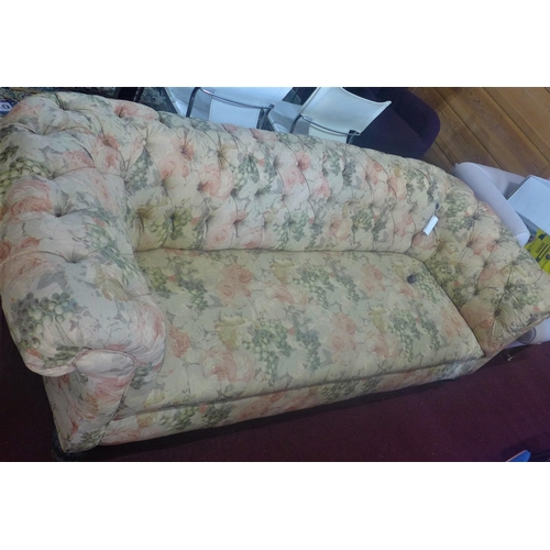 52 - A Victorian 3 seat Chesterfield sofa, with floral upholstery, raised on carved legs and castors...