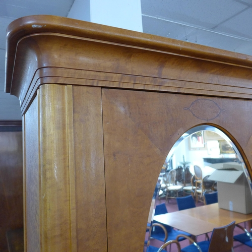 75 - A French walnut armoire with inset bevelled oval mirror plate to door, enclosing adjustable shelves ...