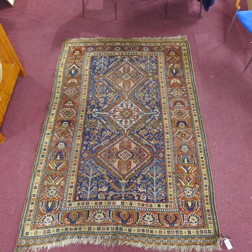 90 - An antique Qashqai carpet with 3 geometric medallions, surrounded by geometric floral motifs on a bl...