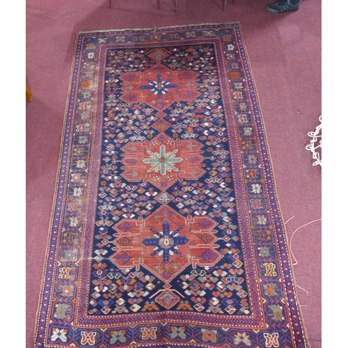 92 - An antique Kazakh carpet with 3 geometric medallions, surrounded by geometric motifs on a blue groun...