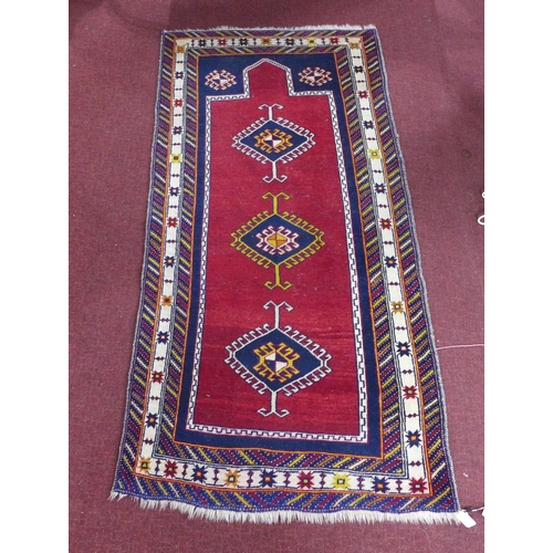 93 - A 20th century Shirvan rug, with 3 geometric medallions on a red ground, contained by geometric bord...