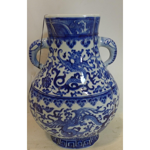 114 - A Chinese blue and white twin handled vase, decorated with dragons and scrolling foliage, bearing Qi...