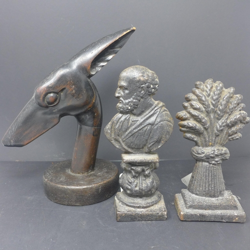 176 - Two Victorian cast iron door stops, together with an Art Deco wood carving of a dog's head...