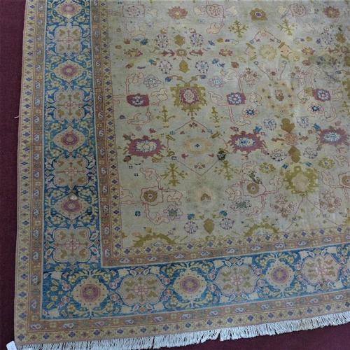512 - A large 20th century Persian carpet with repeating geometric motifs, on a beige ground, contained by...
