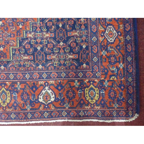 196 - An antique Senneh rug with geometric medallion, surrounded by motifs, on a red and blue ground, circ...