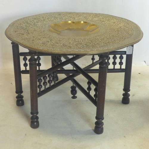 200 - A 20th century Moroccan tea table, with brass tray top on folding base, H.50 D.78cm...
