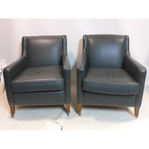 320 - A pair of Regency style green leather upholstered armchairs, raised on tapered legs and castors...