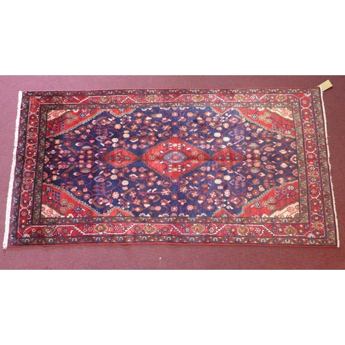 502 - A North-West Persian Nahawand rug, central double pendent medallion with repeating petal motifs on a...