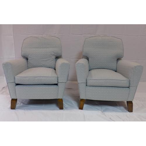 540 - A pair of 20th century armchairs raised on splayed teak feet...
