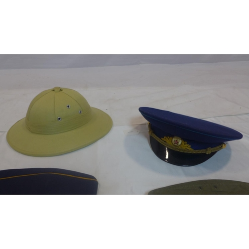 768 - A collection of military hats to include a Blue Russian Soviet military officers cap, a Finnish cap ...