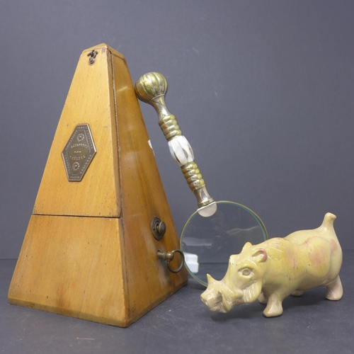 35 - A Maelzel metronome, H.22cm, together with a stone carving of a warthog, H.7 W.12 D.4.5cm, and a bra...