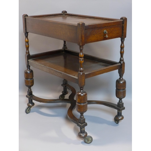 5 - A 20th century oak two tier trolley, single drawer, on turned supports, X-stretcher and castors, H.8...