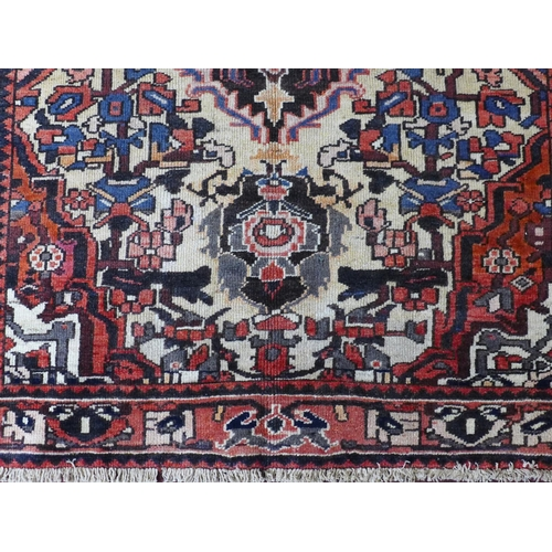 27 - A Central Persian Bakhtiari rug, central double pendant medallion with repeating spandrels on an ivo...