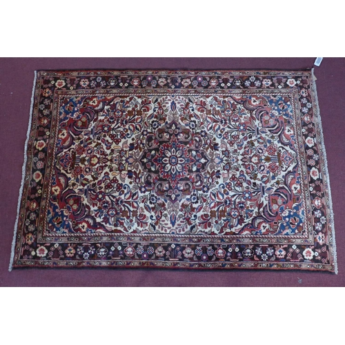 30 - A North-West Persian Lilihan rug, central floral medallion with repeating petal motifs on an ivory f...