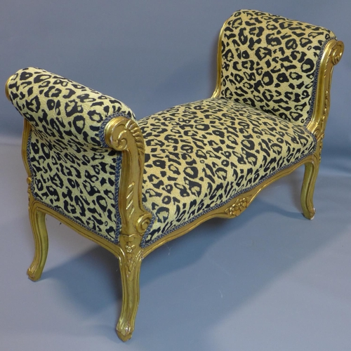 44 - A giltwood window stool with leopard print upholstery, on cabriole legs, H.69 W.107 D.46cm...