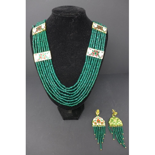 124 - An Indian emerald beaded necklace with enamelled plaques, together with a matching pair of earrings...