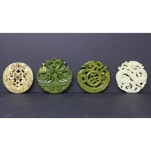 126 - Four Chinese hardstone pendants, carved with dragons, phoenixes and scrolling foliage, largest 8cm d...