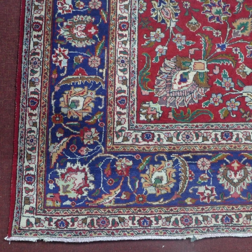 147 - A large Persian Tabriz carpet, stylised floral motifs on a red ground, within stylised floral border...