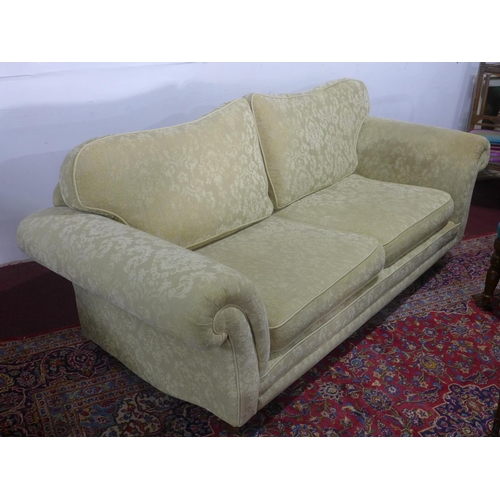 312 - A three seater sofa with cream floral upholstery, raised on sqaure tapered legs and brass caps and c...